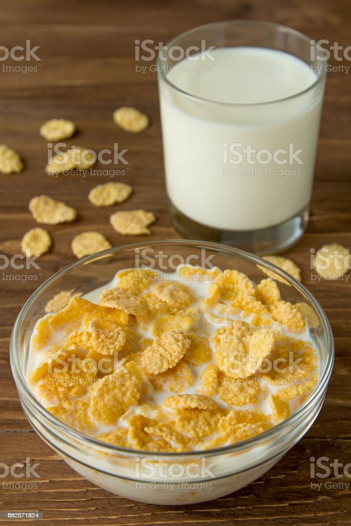 Corn flames in a bowl with milk and glass of milk on wooden surface stock photo