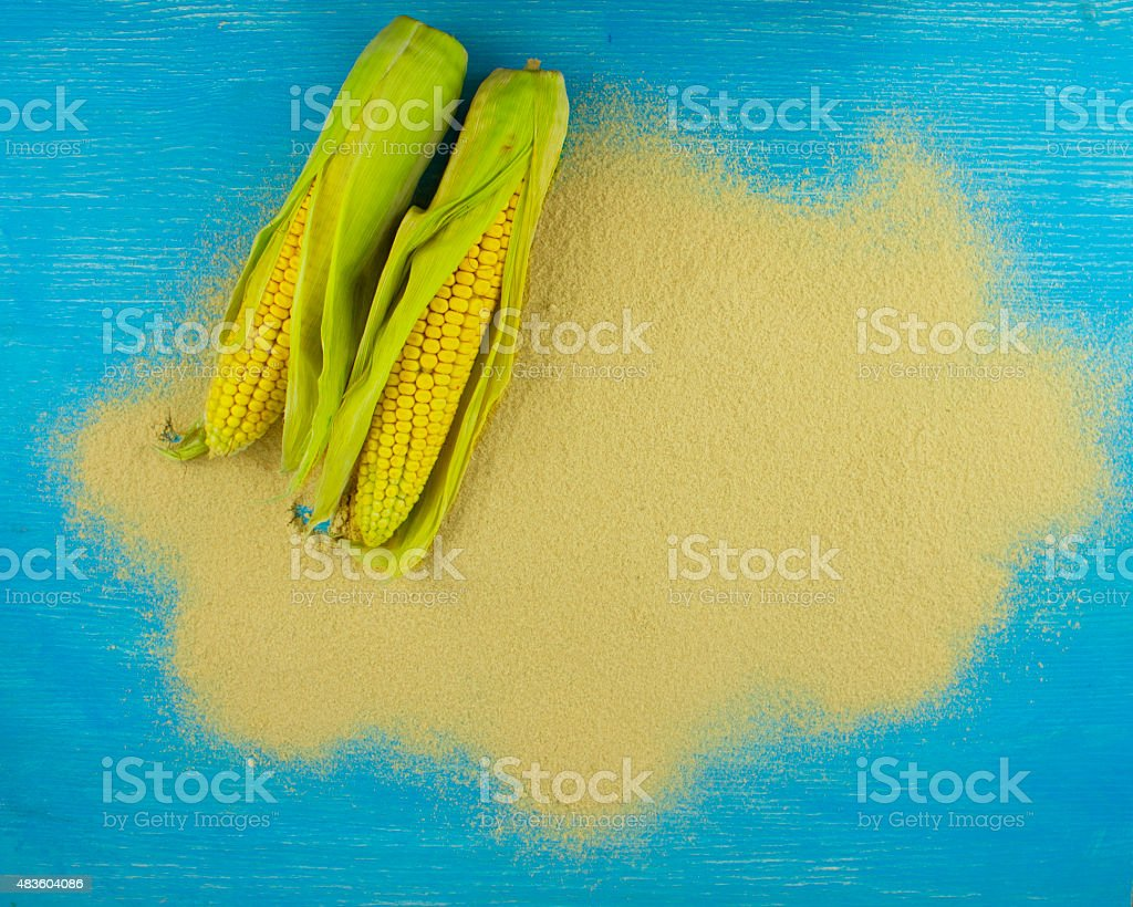 corn flour and corn on the cob on a wooden table stock photo