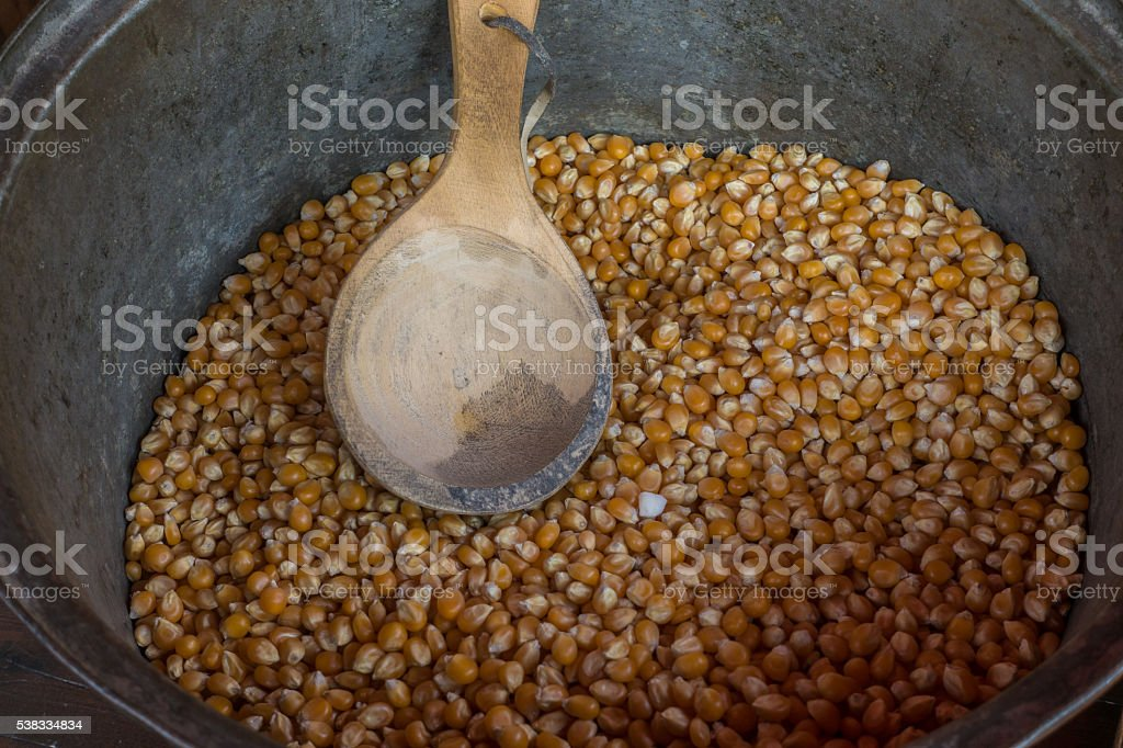 Corn grain in the cauldron with a wooden spoon stock photo