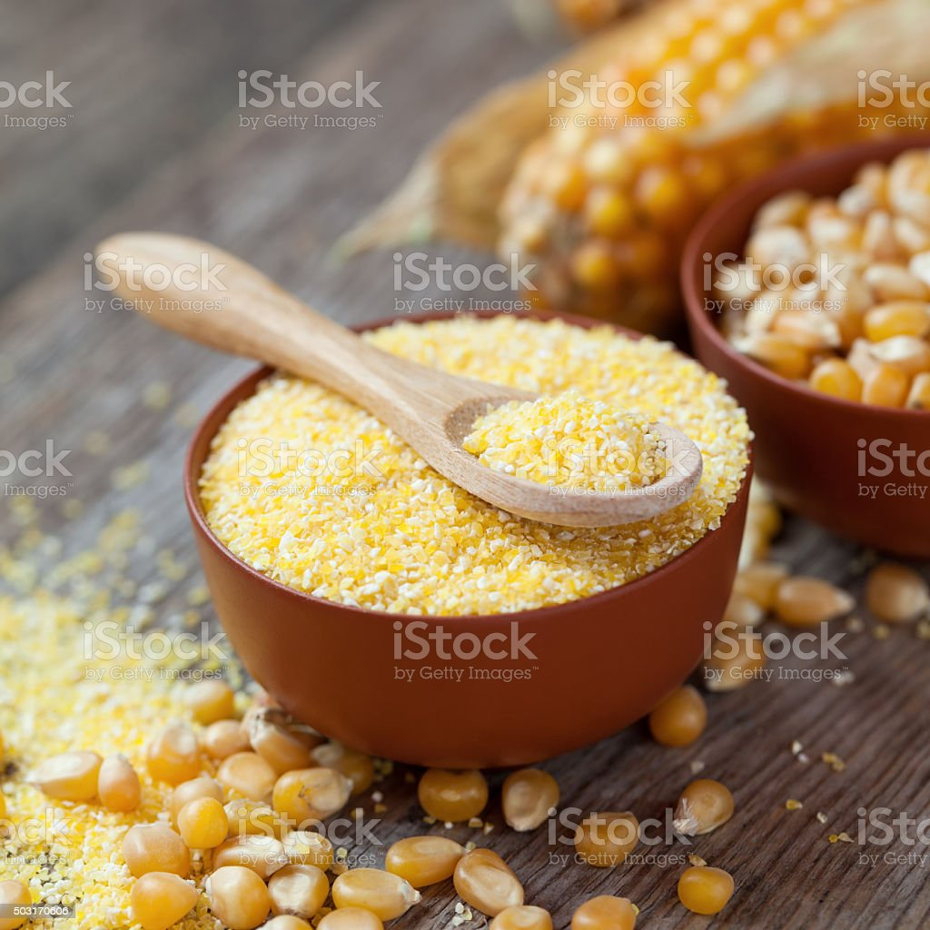 Corn groats  in bowl, corn seeds and corncobs. stock photo