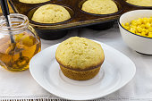 Corn muffin in plate with muffins in pan