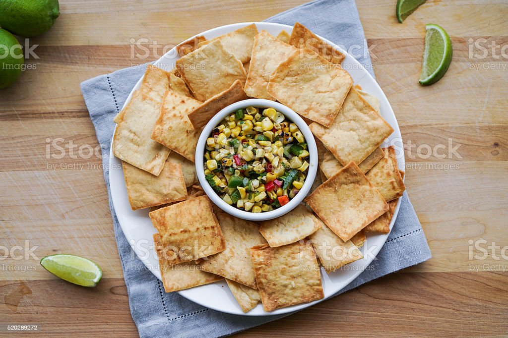 Corn Salsa with Pita Chips on Wood Background. stock photo