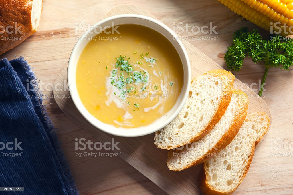 corn soup with sliced bread on wooden board stock photo