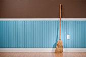 Corn whisk broom standing in empty room
