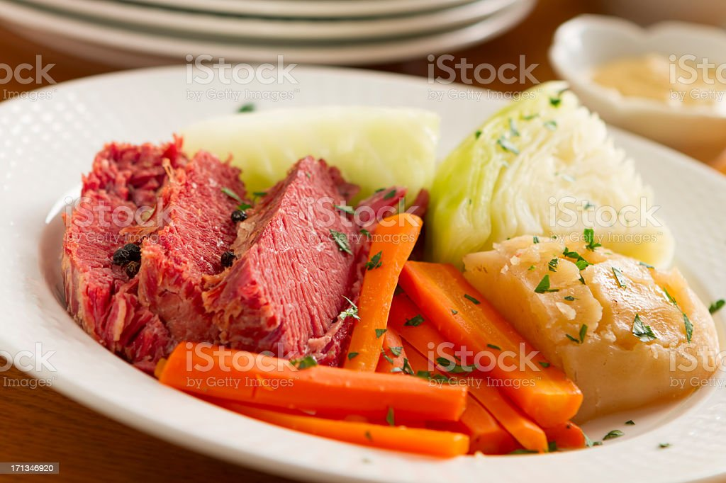 Corned beef, carrots, and onion on a white plate stock photo