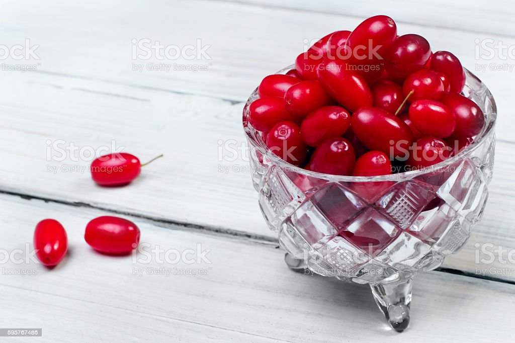 Cornel berries crystal glass on white wooden background, selecti stock photo