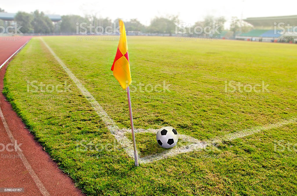 Corner flag with ball on a soccer field stock photo