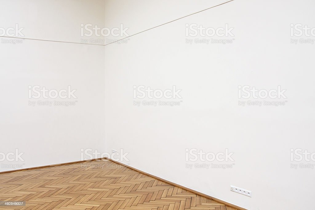Corner of a large white wall with wooden floor tiles stock photo