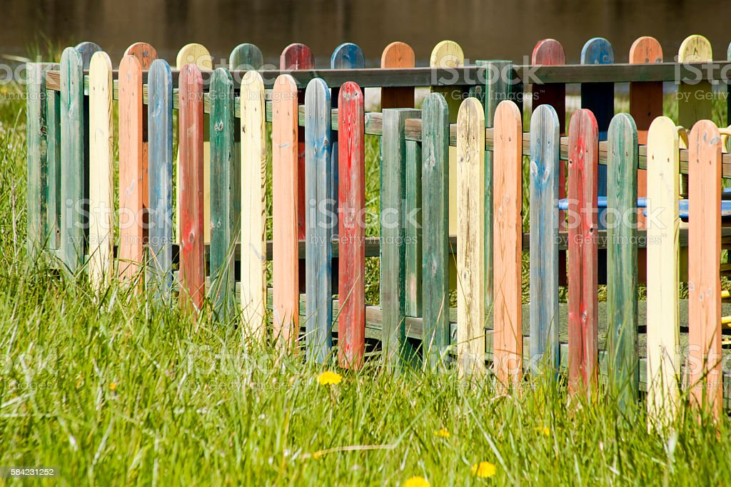 Corner of multicolored wooden fence stock photo
