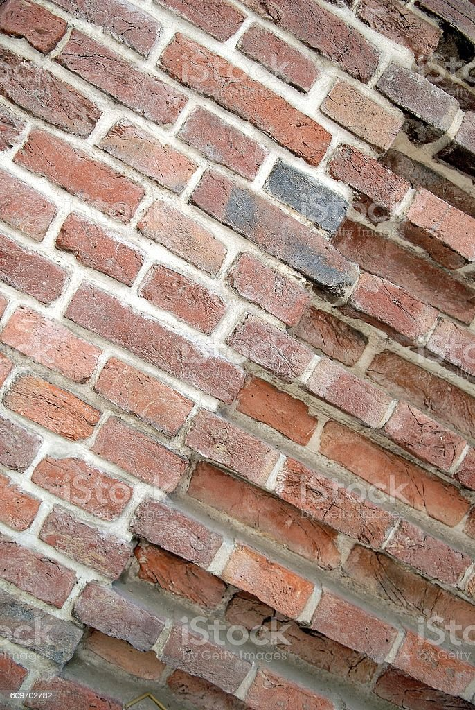 Corner of red brick wall with different prominence stock photo