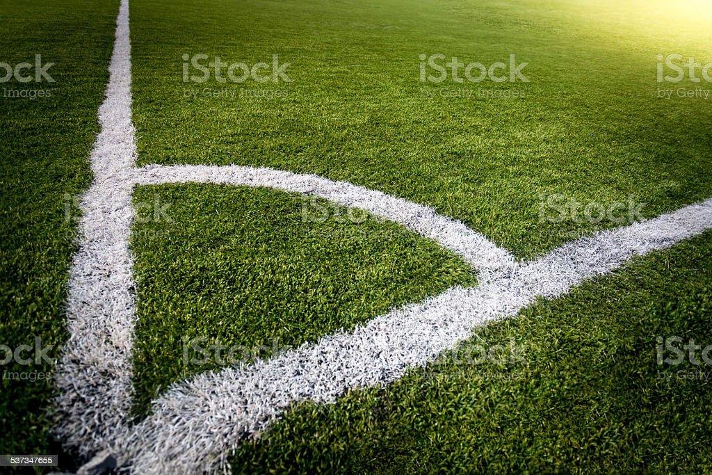 corner of soccer field lit by sun rays stock photo
