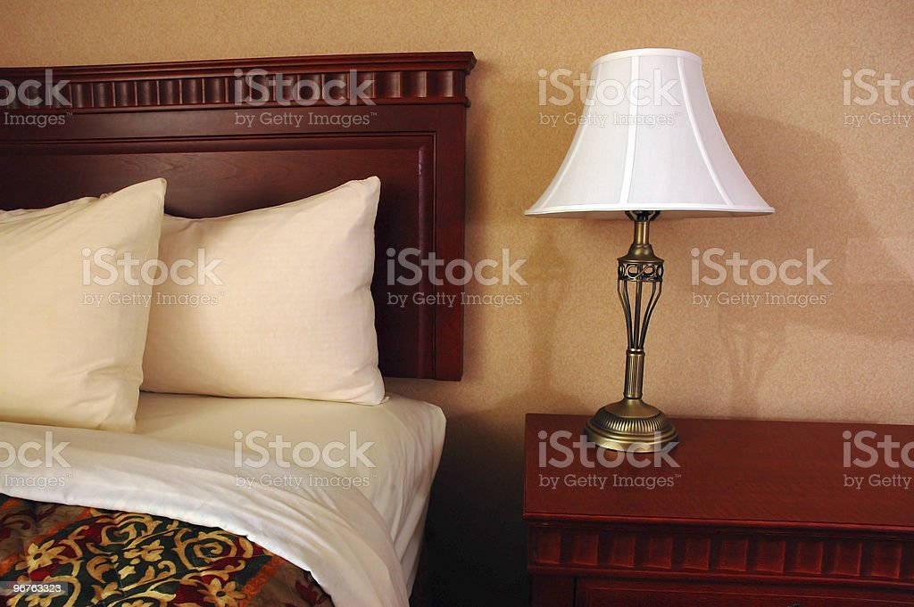Corner view of bed and bedside table and lamp in hotel room stock photo