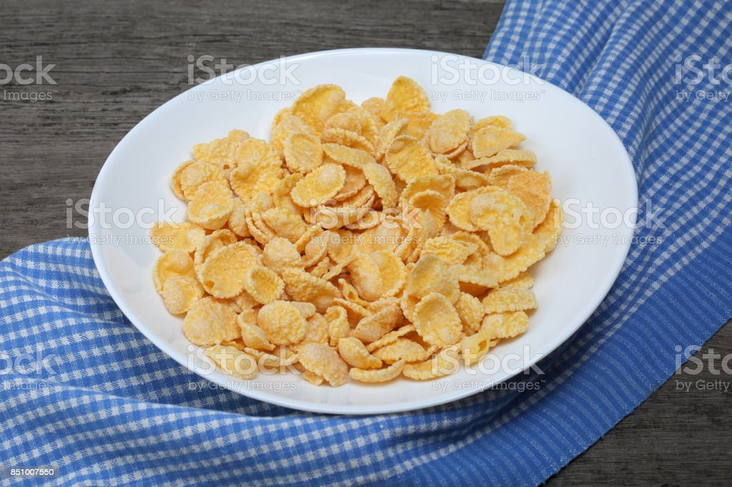 Cornflakes in plate with napkin on wood background stock photo