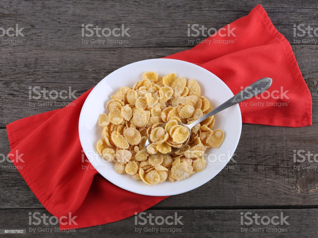 Cornflakes in plate with red napkin on wood background stock photo