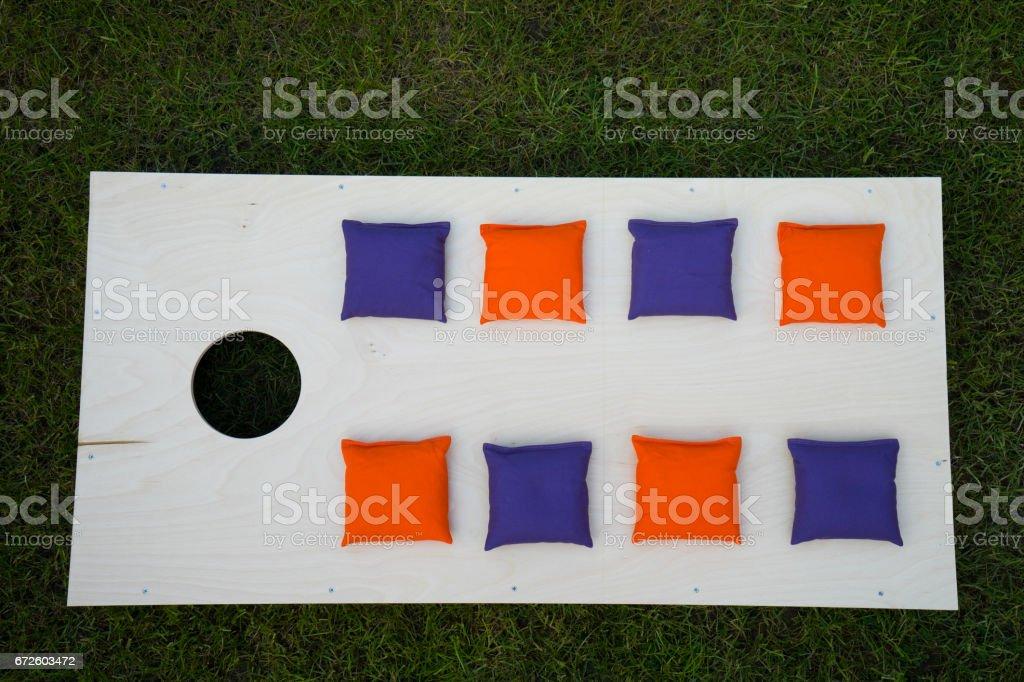 Cornhole Board Flat Lay with beanbags on grass stock photo