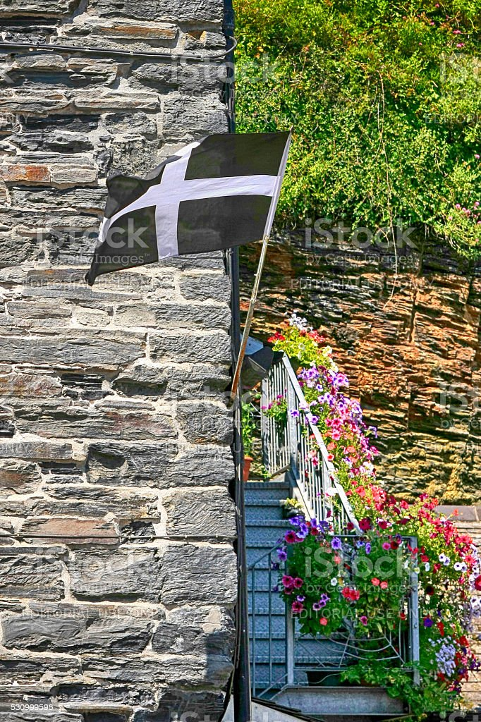 Cornish flag flies from a wall in Boscastle, Cornwall, UK stock photo