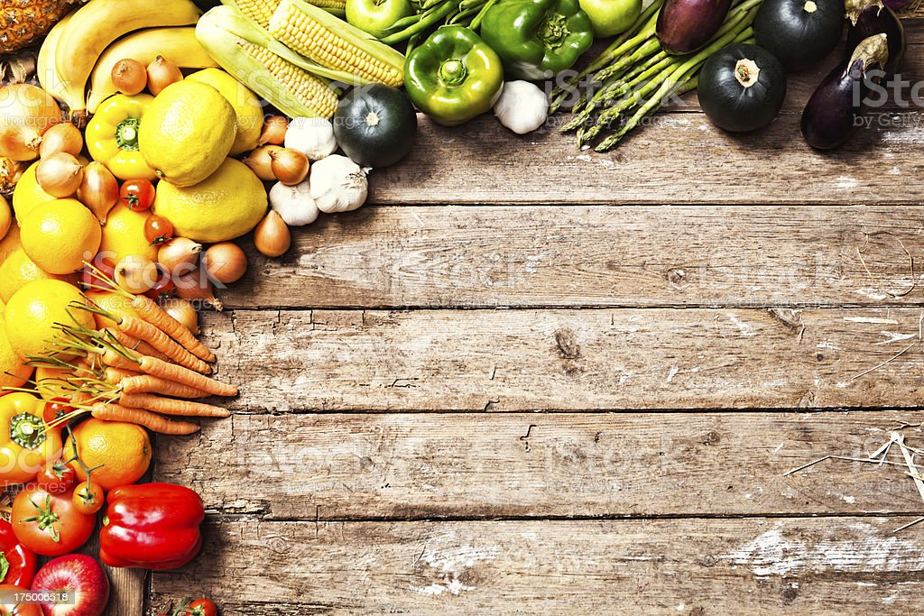Cornucopia of fresh vegetables form border on weathered wood royalty-free stock photo