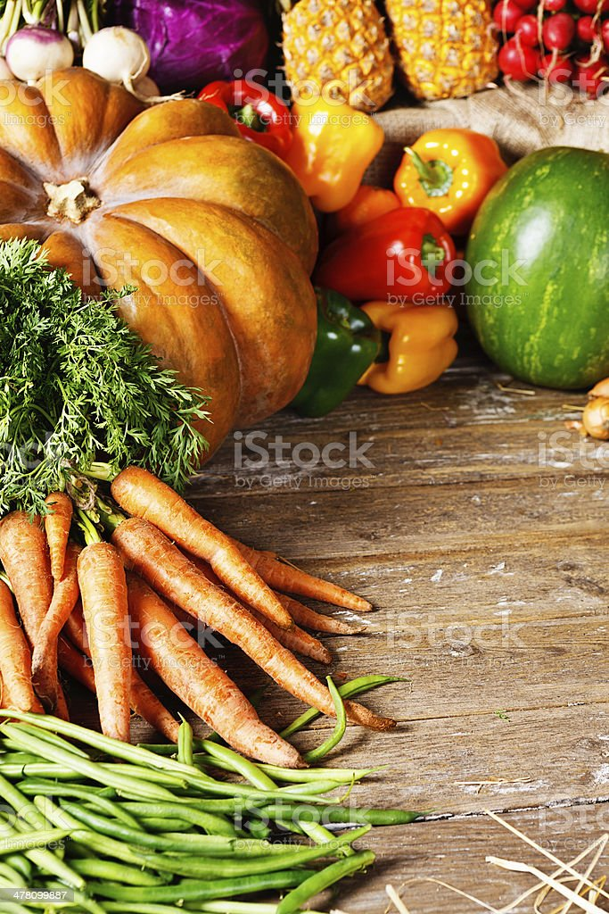 Cornucopia of mixed fresh vegetables on worn wooden background royalty-free stock photo