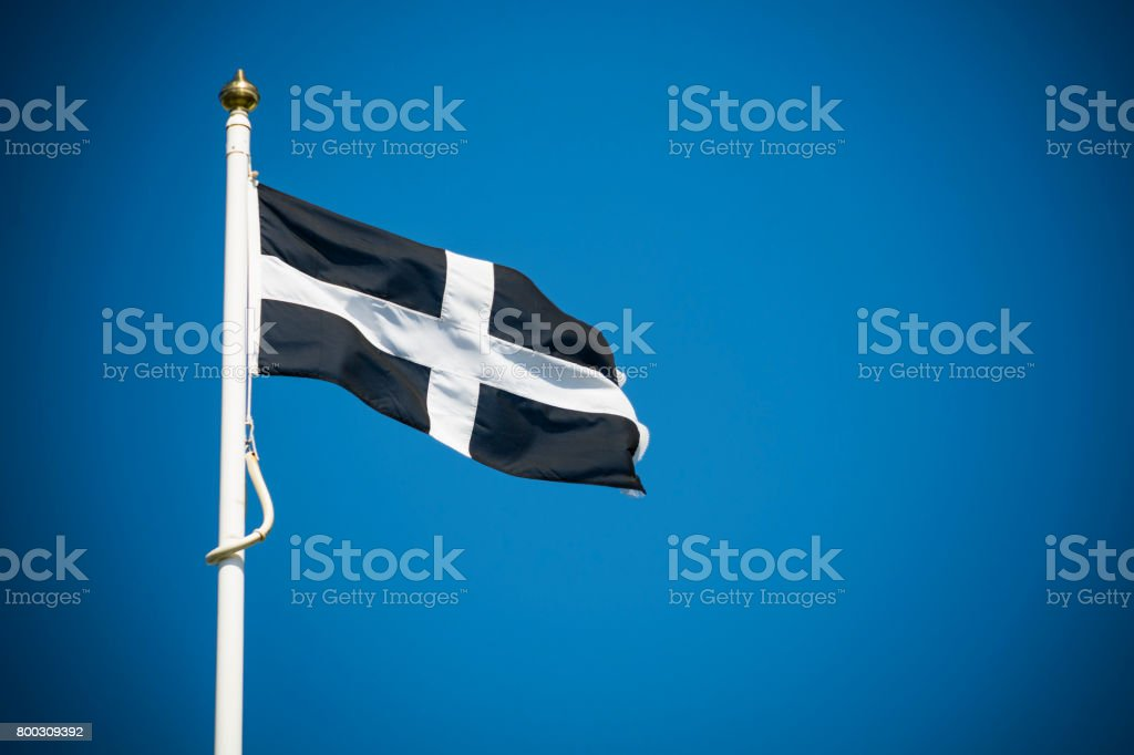 Cornwall flag flying against clear blue sky background stock photo