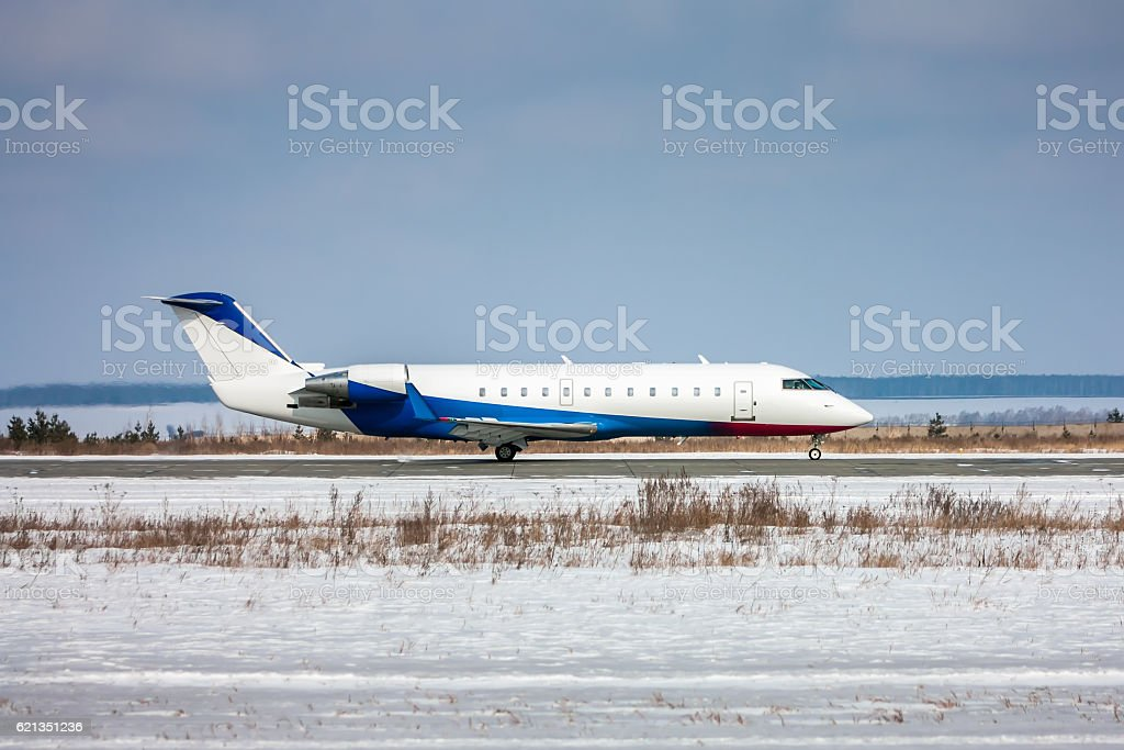 Corporate aircraft taxiing on the runway in winter airport royalty-free stock photo