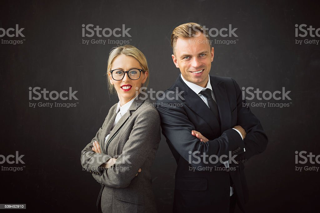 Corporate business man and woman standing with their hands crossed stock photo