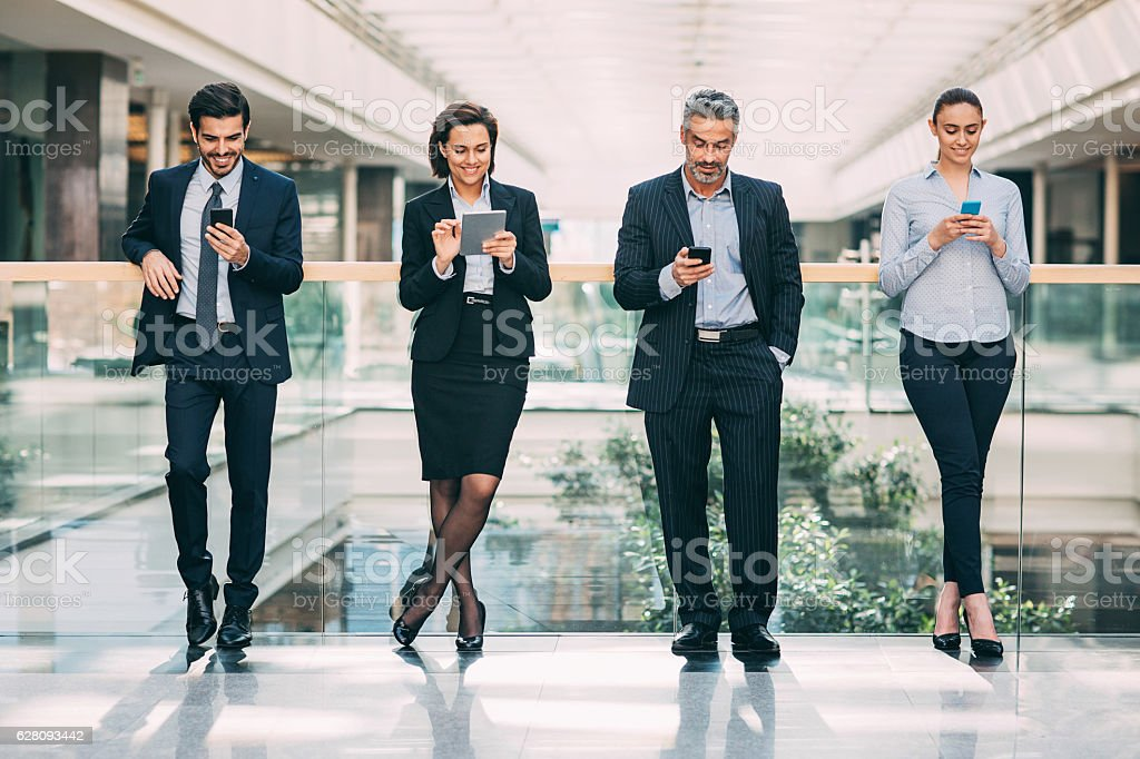 Mature businessman with his younger team using smart phones and...