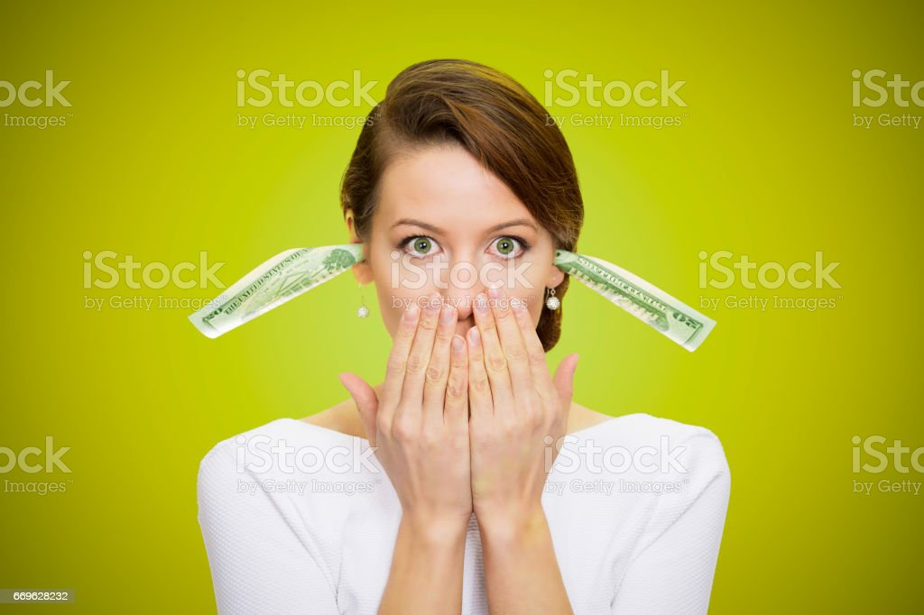 Corporate businesswoman plugs her ears with dollar banknotes, bills, covers her mouth stock photo