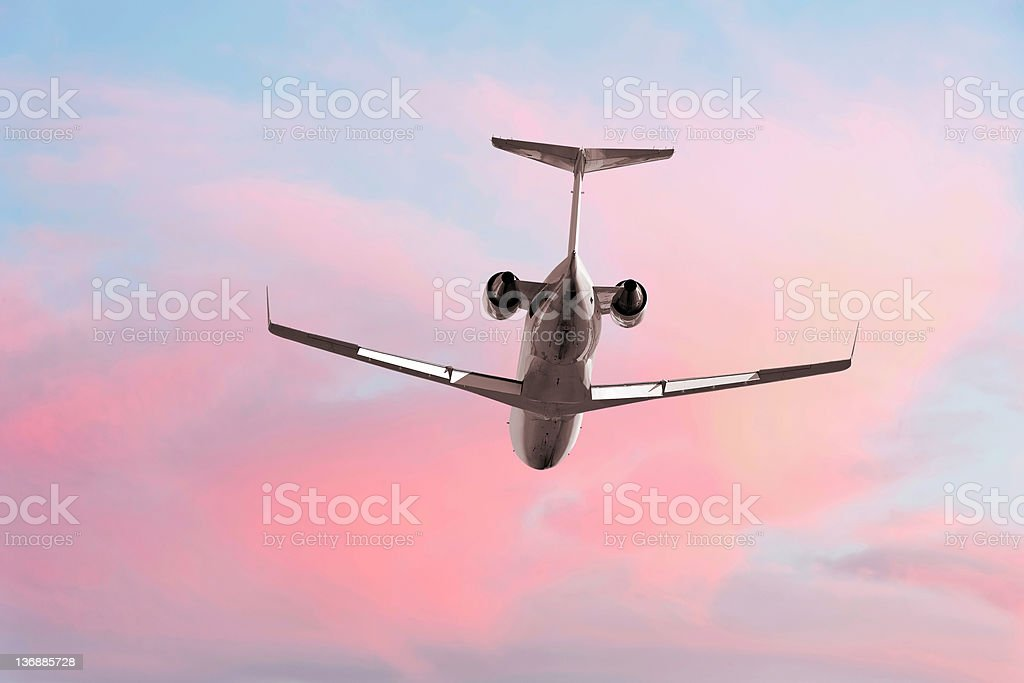XXL corporate jet airplane flying at dusk stock photo