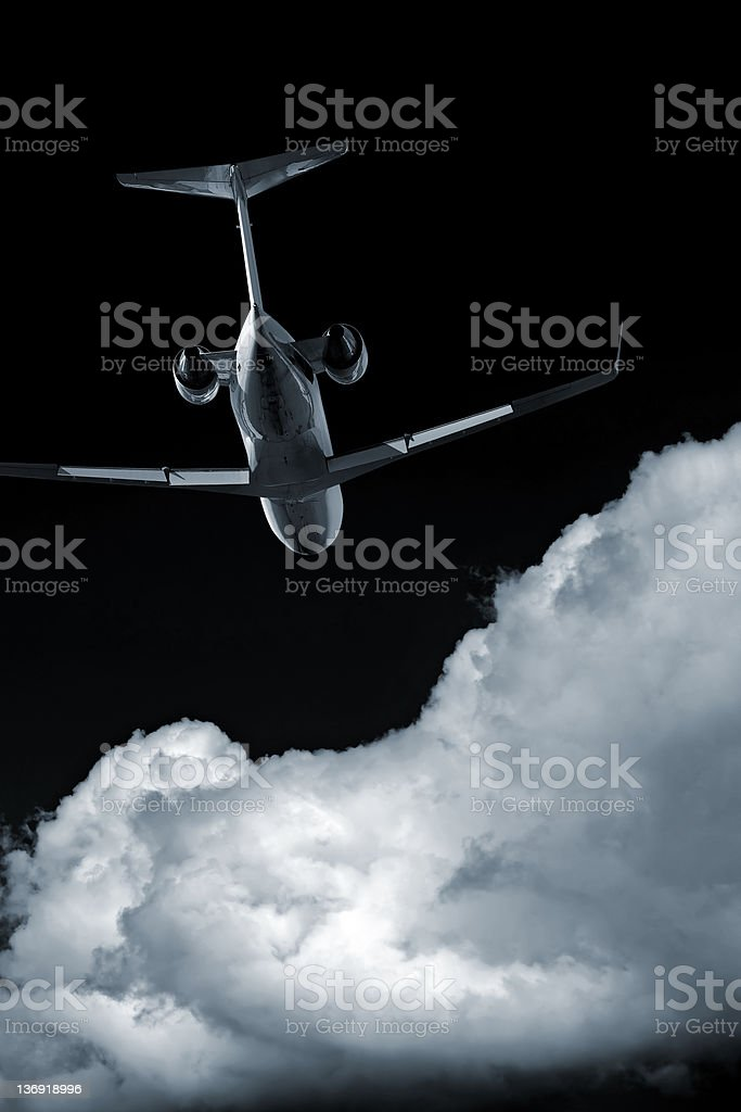 XL corporate jet airplane flying at night royalty-free stock photo