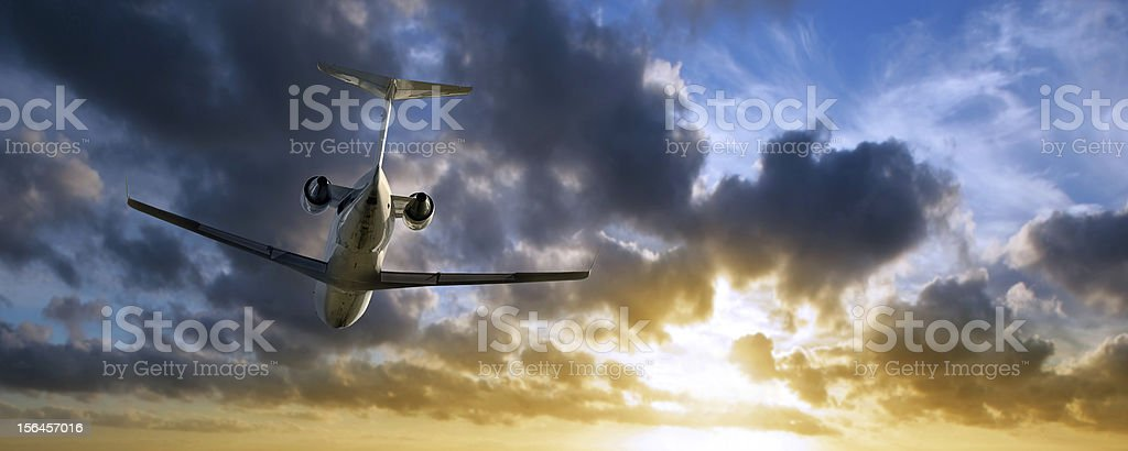 XXL corporate jet airplane flying at sunset stock photo