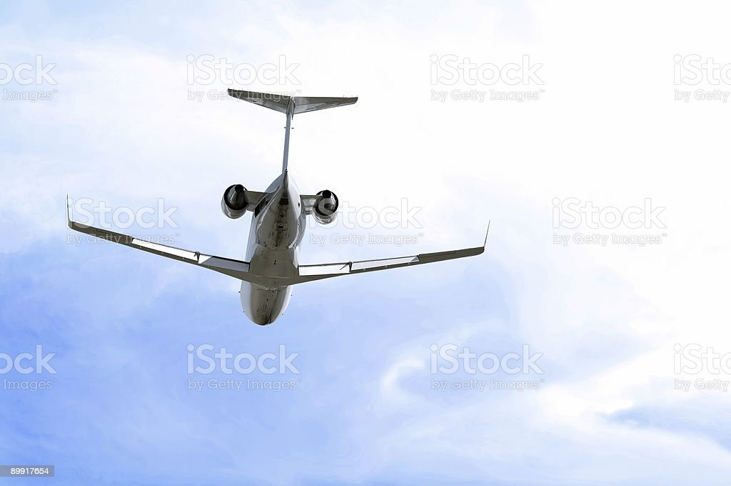 XXL corporate jet airplane flying in bright sky stock photo