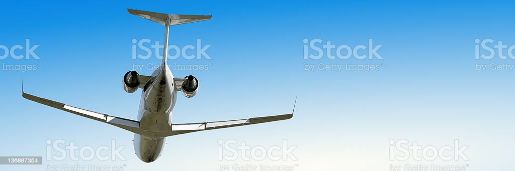 corporate jet airplane flying in clear blue sky royalty-free stock photo