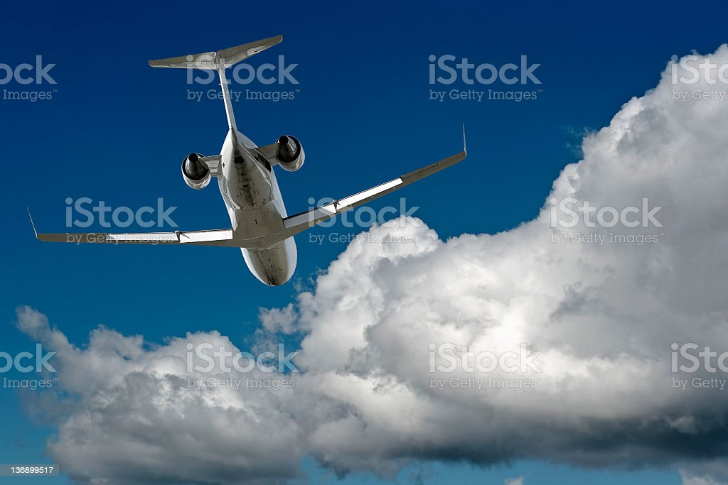 corporate jet airplane flying in cloudy sky royalty-free stock photo