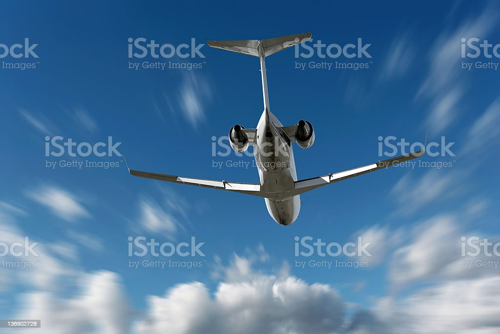 XL corporate jet airplane flying in motion blur sky stock photo