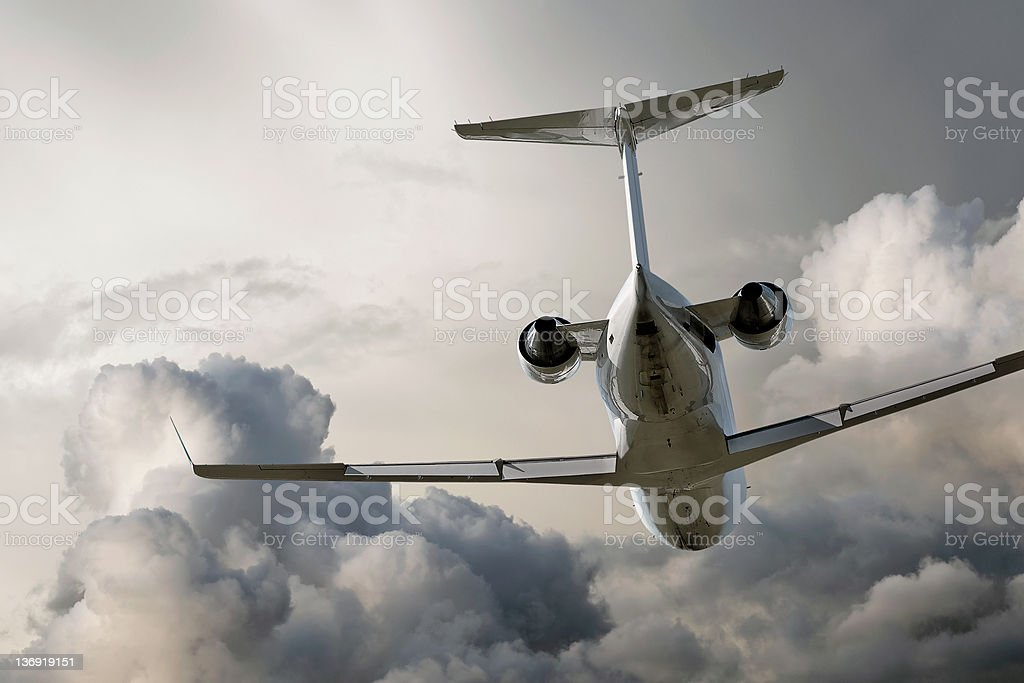 corporate jet airplane flying in storm stock photo