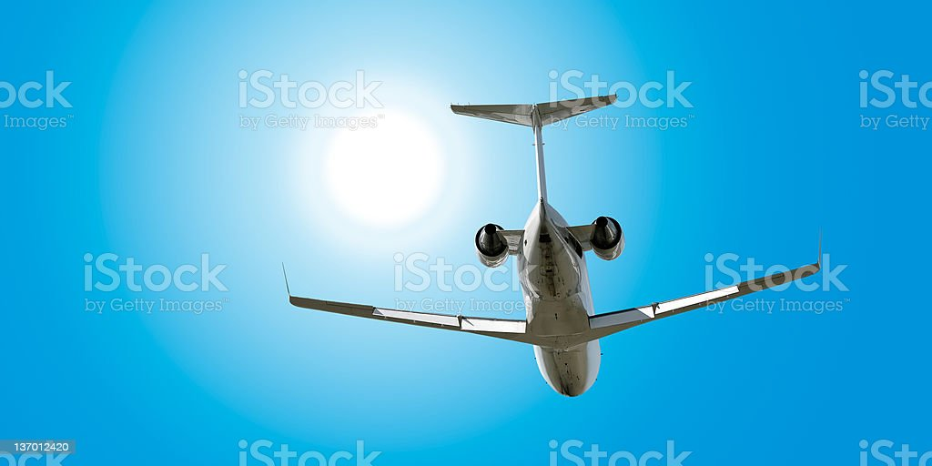 XL corporate jet airplane flying in sunny sky royalty-free stock photo