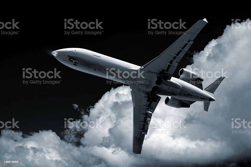 XL corporate jet airplane landing at night stock photo