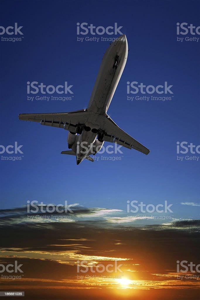 corporate jet airplane landing at sunset stock photo