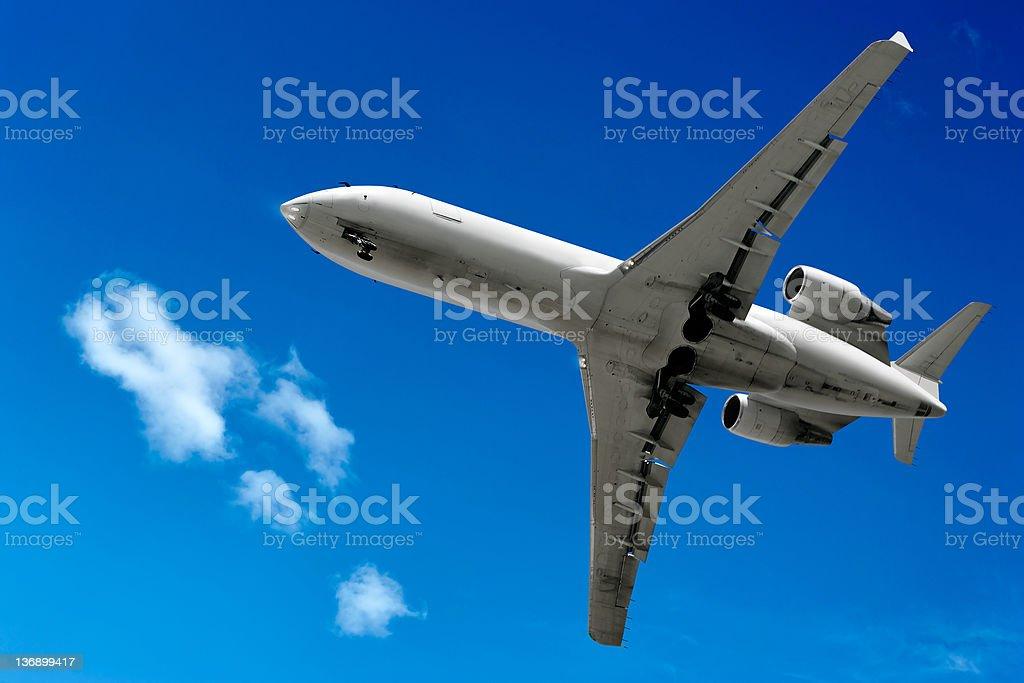 corporate jet airplane landing in bright sky stock photo