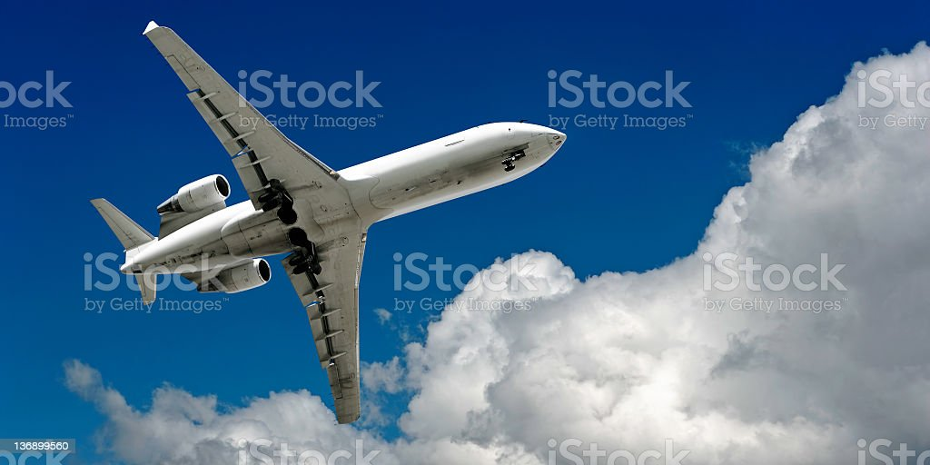 corporate jet airplane landing in cloudy sky royalty-free stock photo