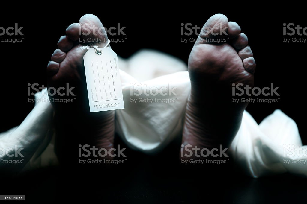 Corpse with toe tag on persons foot stock photo