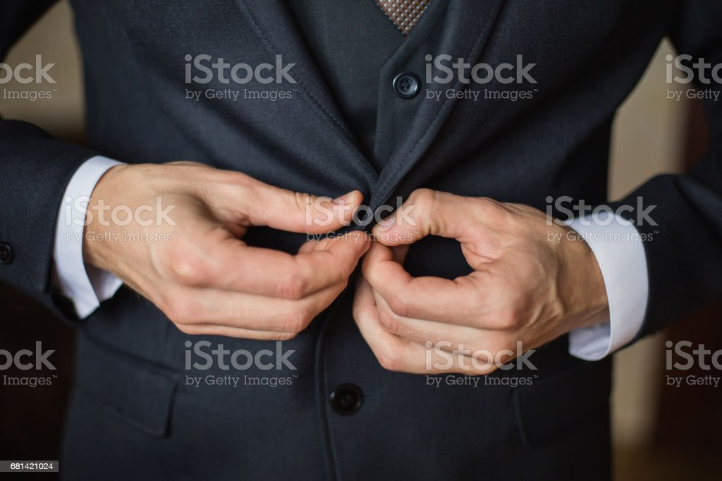correct button on jacket, hands close-up, dressing, man's style, correcting sleeves,  preparing for the wedding stock photo