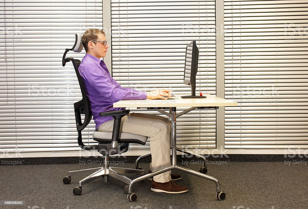 correct sitting position at workstation with computer stock photo