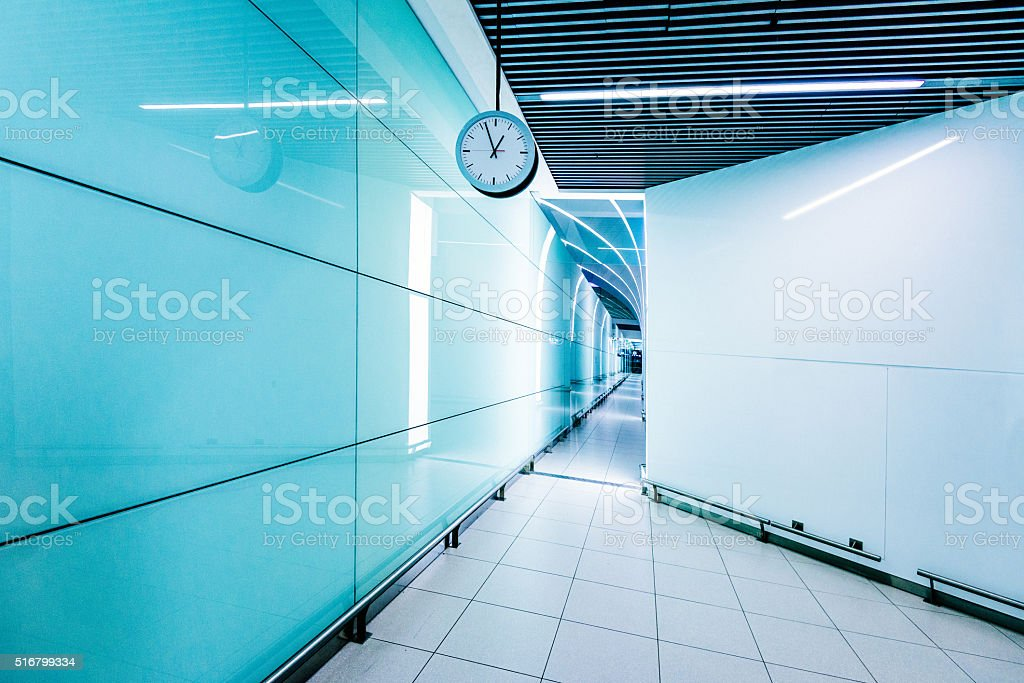 Corridor in modern building with analogue clock in blue tone stock photo