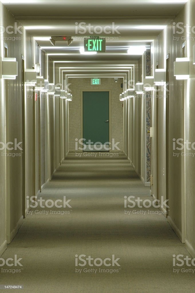 Corridor with a green emergency exit door at the end stock photo