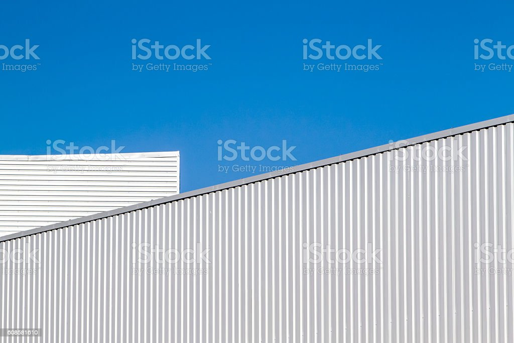 Corrugated sheet metal wall and roof against blue sky. Modern stock photo