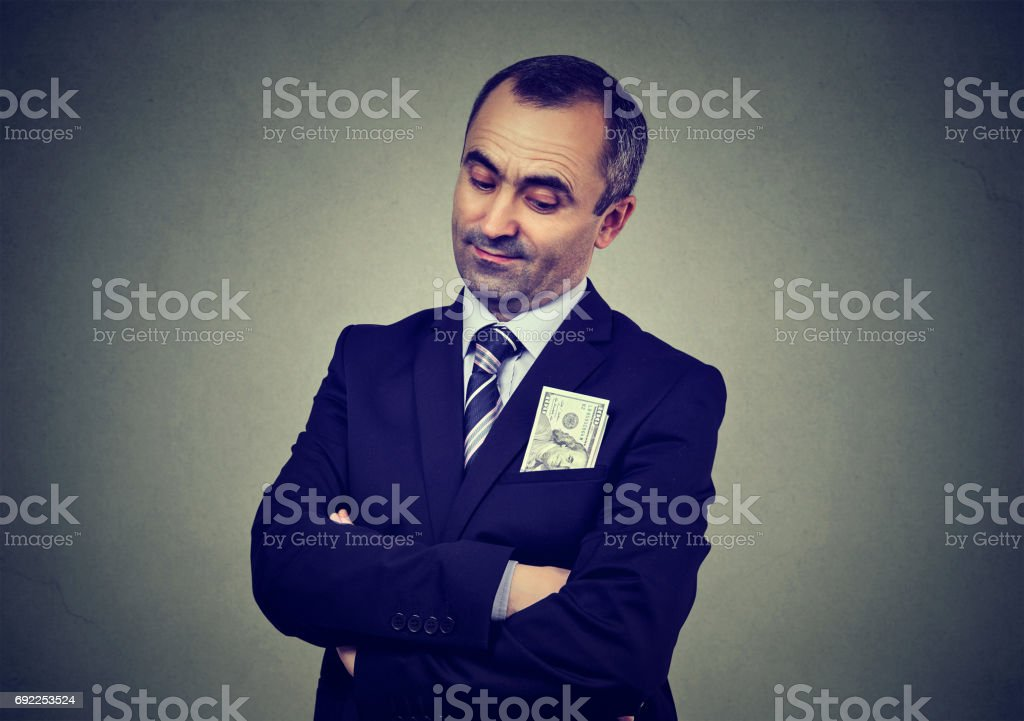 Corrupt businessman with bribery money in suit pocket stock photo