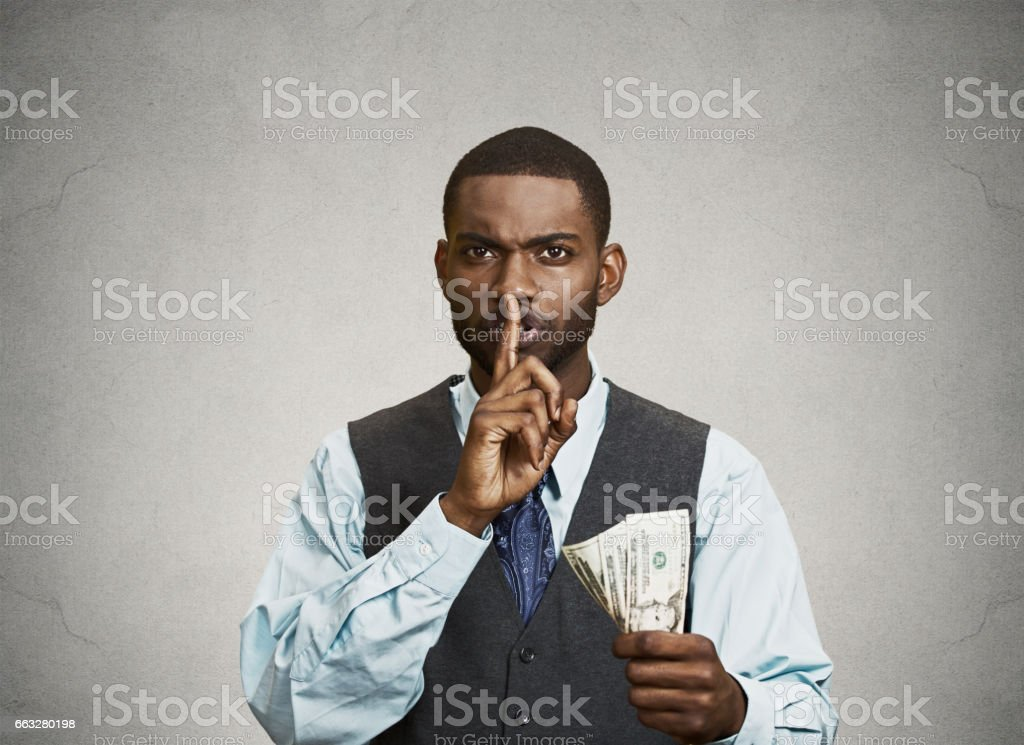 corrupt guy businessman holding dollar bill in hand showing shhh sign stock photo