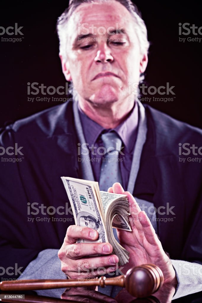 Corrupt judge slyly counting bribe money in courtroom stock photo