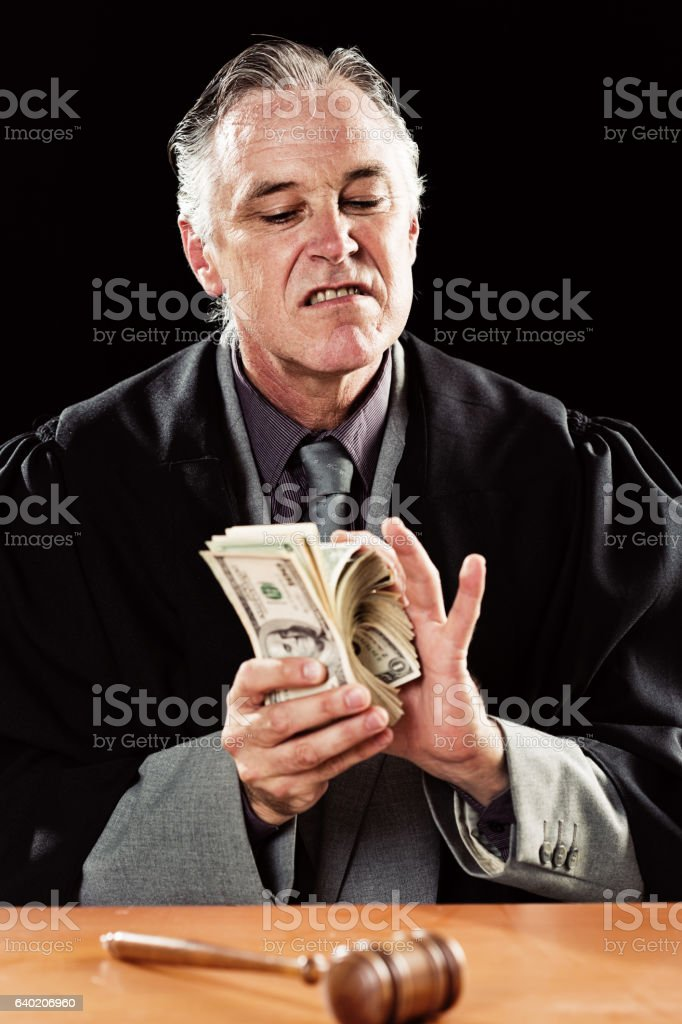 Corrupt judge smirks, looking down and counting out dollars gleefully stock photo